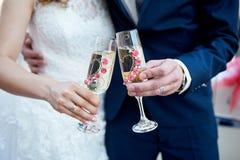 Os noivos estão guardando vidros do champanhe Fotografia de Stock