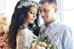 Os noivos estão preparando-se na manhã para o casamento Pares loving que abraçam em casa Noivo considerável e noiva encantador Imagem de Stock