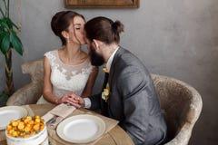 Os noivos estão sentando-se na tabela na tabela A noiva está beijando o noivo na testa foto de stock royalty free