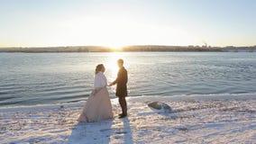 Os noivos felizes banham-se nos raios do sol de ajuste na costa do rio no inverno filme