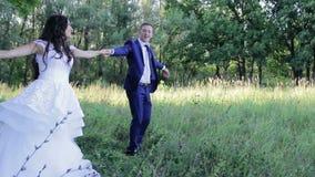Os noivos felizes estão dançando no parque dentro video estoque