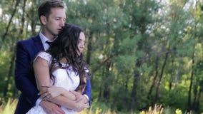 Os noivos felizes estão dançando no parque no seu filme