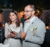 Os noivos no corte do partido e para tentar o bolo de casamento fotografia de stock royalty free