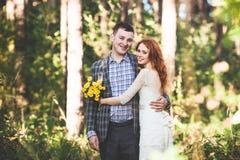 Os noivos que abraçam-se na floresta Imagem de Stock Royalty Free