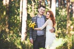 Os noivos que abraçam-se na floresta Imagens de Stock Royalty Free