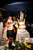 Os noivos que cortam o bolo na cerimônia da celebração Imagens de Stock