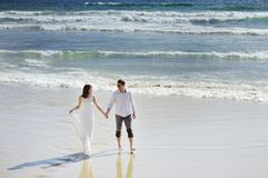 Os noivos que guardam as mãos aproximam o mar no dia do casamento imagens de stock