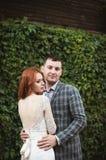 Os noivos que levantam perto de uma cerca verde e de uma casa velha Imagem de Stock