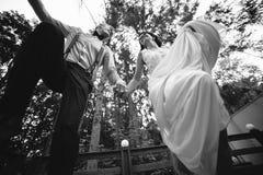 Os noivos que saltam, tendo o divertimento Fotografia de Stock