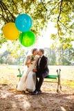 Os noivos sentam-se no banco com balões Fotografia de Stock