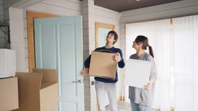 Os novos proprietários da casa bonita estão indo para dentro com caixas da caixa, olhando ao redor com excitamento e beijo vídeos de arquivo