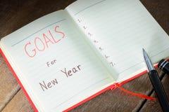 Os objetivos de ano novo com caderno e pena Fotos de Stock