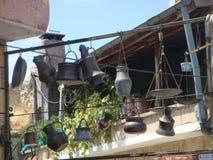 Os objetos da cozinha no ferro fundido suspenderam em um pátio Turquia Imagens de Stock