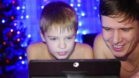 Os olhares da criança e do pai à tabuleta que encontra-se na cama No fundo ilumina festões video estoque