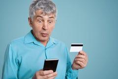Os olhares de cabelo cinzentos chocados do homem com expressão frustrante no telefone esperto, podem o ` t compreender como aplic Fotografia de Stock