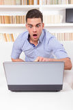 Os olhares do homem surpreendidos no índice no computador monitoram a falha Fotos de Stock