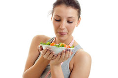Os olhares novos da menina da aptidão em uma grande placa da salada nas mãos estão em um fundo branco Imagem de Stock Royalty Free