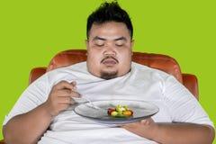 Os olhares obesos do homem hesitam comer a salada no estúdio imagem de stock