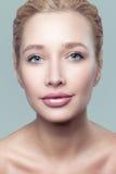 Os olhos azuis bonitos da jovem mulher do retrato da beleza limpam a cara da pele fotos de stock royalty free