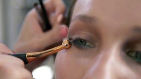 Os olhos compõem o processo O artista corrige a linha do olho usando uma escova profissional com borda dourada Feche acima de uma filme