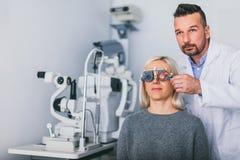 Os olhos da mulher de exame do ótico imagens de stock