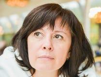 Os olhos de meia idade do marrom da mulher estão sentando-se no apartamento foto de stock