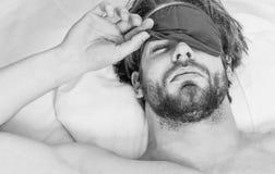 Os olhos do homem são fechados com abrandamento Imagem que mostra o homem novo que estica na cama Pés do homem que dormem em conf imagem de stock
