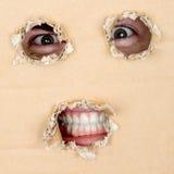 Os olhos e os dentes olham para fora do furo Imagem de Stock Royalty Free