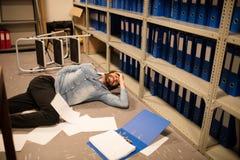 Os originais dispersaram pelo homem de negócios caído na sala de armazenamento do arquivo imagens de stock