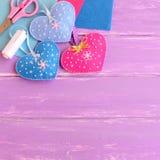 Os ornamento ajustados, tesouras dos corações de feltro, linha, agulhas, feltro cobrem no fundo de madeira lilás com espaço vazio Imagem de Stock