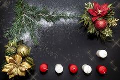 Os ornamento do Natal com as flores douradas e vermelhas, as bolas brilhantes e um pinho ramificam foto de stock