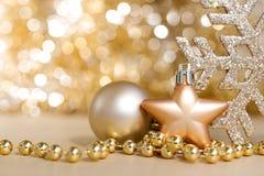 Os ornamento do Natal com ouro circundam o backgro claro da faísca do bokeh Fotos de Stock