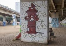 os ossos da Fogo-boca de incêndio e de cão na casca estacionam Ellum central, profundo, Texas imagem de stock