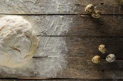 Os ovos amassados da massa e de codorniz em uma tabela de madeira espanaram com farinha Imagem de Stock