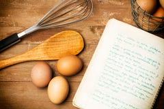 Os ovos, a colher de madeira e um cozinheiro registram Fotos de Stock