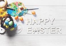 Os ovos coloridos e outras decorações em uma tabela de madeira branca com PÁSCOA FELIZ assinam Fotos de Stock