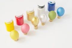 Os ovos coloridos puseram sobre a pilha de moedas de ouro com garrafa Imagens de Stock Royalty Free
