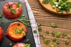 Os ovos com alecrins e manjericão cozeram no tomate, vista superior Imagens de Stock