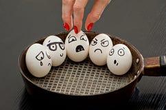 Os ovos com emoções pintadas em uma frigideira, uma mão fêmea tomam um delas Foto de Stock