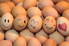 Os ovos com símbolo feliz da face e do coração no por do sol iluminam-se Foto de Stock Royalty Free