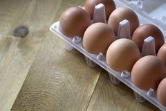 Os ovos crus da galinha de Brown estão em um pacote para ovos em uma tabela marrom Fotos de Stock Royalty Free