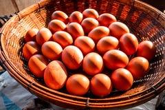 Os ovos da galinha de Brown arranjaram na cesta do rattan com a luz solar que brilha neles imagens de stock royalty free