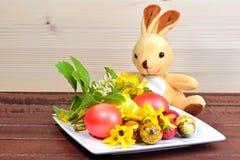 Os ovos da páscoa, as flores da mola e um coelho brincam Fotos de Stock Royalty Free
