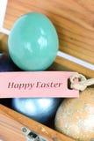 Os ovos da páscoa coloridos com papel feliz do texto da Páscoa etiquetam Fotografia de Stock Royalty Free