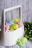 Os ovos da páscoa coloridos do laço com fita curvam-se na cesta de madeira branca imagens de stock