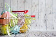 Os ovos da páscoa coloridos do laço com fita curvam-se no cesto de compras foto de stock