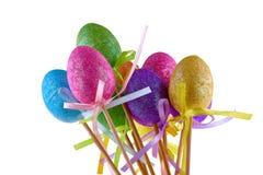 Os ovos da páscoa coloridos em varas isolaram o branco Foto de Stock