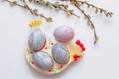 Os ovos da páscoa coloridos encontram-se em uma placa sob a forma de uma galinha em um fundo branco com um ramalhete de ramos do  Fotos de Stock Royalty Free