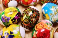 Os ovos da páscoa com pintura original estão na cesta na tabela Fotos de Stock