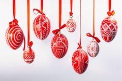 Os ovos da páscoa com teste padrão ucraniano popular penduram em fitas vermelhas da parte superior no fundo branco Ovos tradicion Imagem de Stock